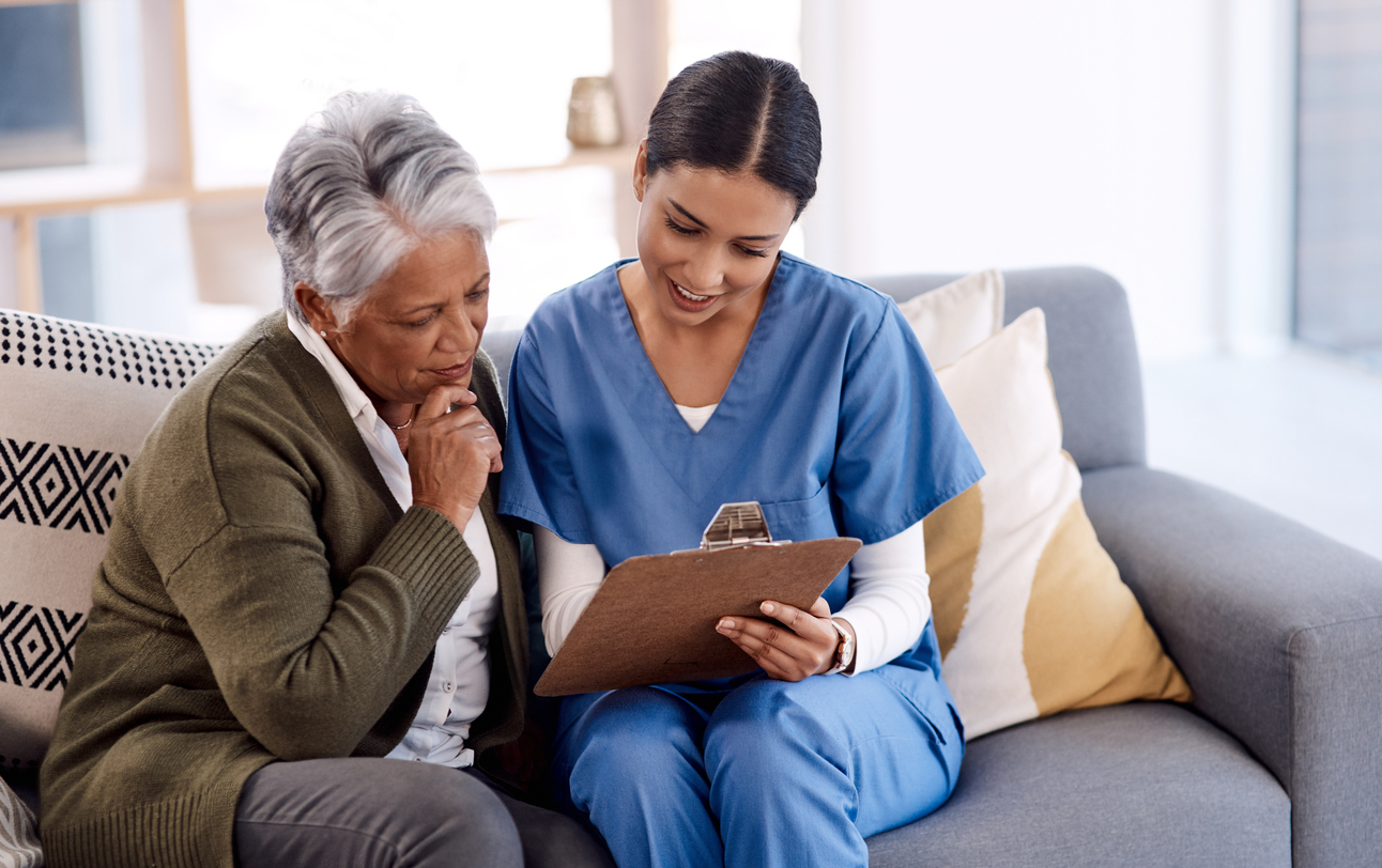 Black senior citizen reviewing her health coverage plan with a nurse in scrubs